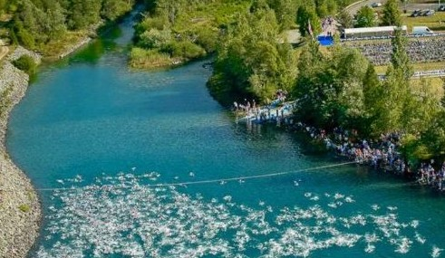 A sprawling mass of swimmers heading past the start line out into the lake
